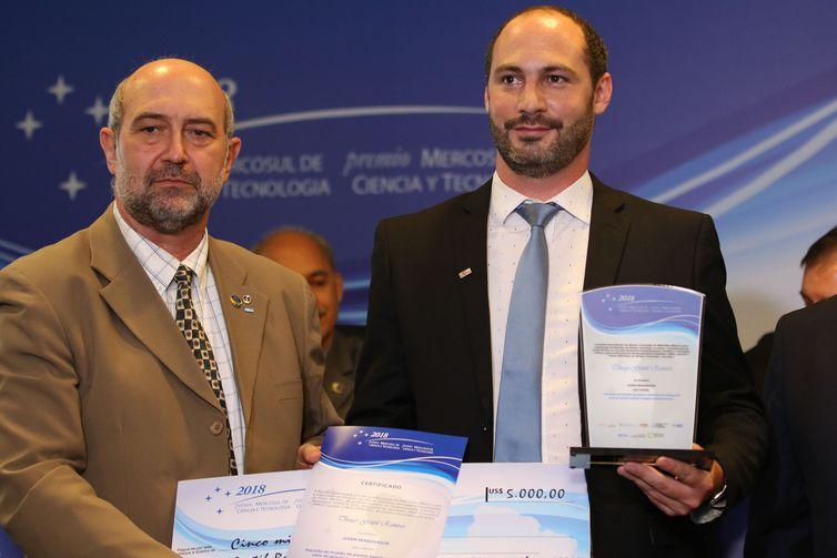 O presidente do CNPq, João Luiz Filgueiras de Azevedo, entrega o prêmio na categoria Jovem Pesquisador a Thiago Gentil Ramires, durante cerimônia de entrega do PrêmioMercosulde Ciência e Tecnologia 2018