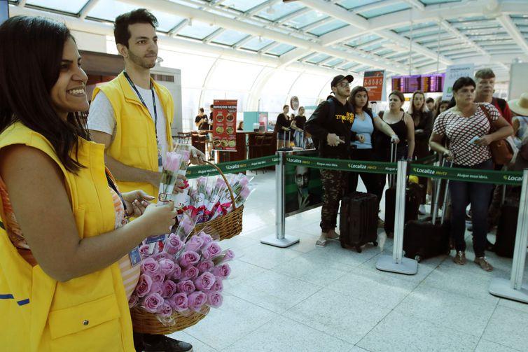 Funcionários da Infraero distribuem rosas na área de embarque, durante a campanha Outubro Rosa no Aeroporto Santos Dumont, para alertar sobre o câncer de mama.